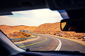 Driving a car on the mountain road in the desert. View of sandstone mountains through the windscreen. The road from Arad to the Dead Sea. Israel