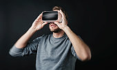 young man wearing Virtual Reality goggles VR Headset on black background