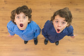 The two little twin with surprised emotion. View from above