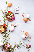 Easter background with various eggs, bunny ears napkin, spring blossom branch,  candies and Easter letter E on the textured surface