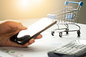 E-commerce and Online shopping concept. Hand holding mobile phone typing online order to shopping with trolley cart.