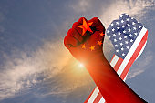 Across of hands of USA flag and China flag. It is symbol of tariff trade war which both countries increase tax barrier for export and import product.