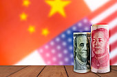 US dollar and Yuan banknote array on wooden table on blurred crack of USA flag and China flag .It is symbol of tariff trade war crisis between USA and China.