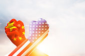 USA and China flag print screen on arm wrestle with sky background.United States of America versus China trade war disputes concept. - Image