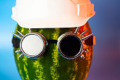 watermelon in the rocker glasses and a hard hat on blue background.