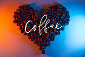 coffee beans are highlighted with neon lined in the shape of a heart