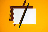 a blank sheet of Notepad, black pencil and hard shadows on bright yellow background