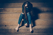Young drunk woman sitting outside in night. Alcoholism and drug addiction lead to depression