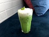 Ice green tea latte with milk on top on navy blue soft sofa in the cafe.