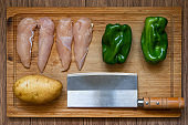 Chicken breast, green peppers, potatoes and kitchen knife on a cutting board