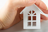 The concept of home, family values. Female hand holds wooden white toy house