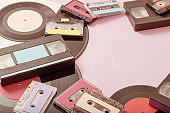 Collection of music tapes, records and video cassettes on paper background. Retro concept
