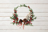 Christmas wreath on white wooden backdrop