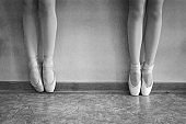 Close-up of ballerina feet on pointe shoes in the dance hall. Vintage photography.
