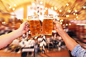 Two people clinking beer glasses at the Oktoberfest - Blurred motion background