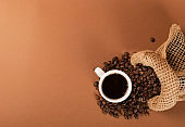 Hot coffee cup and coffee beans on brown background top view