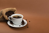 Hot coffee cup and coffee beans in burlap bag
