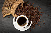 Hot coffee cup and coffee beans on black background top view