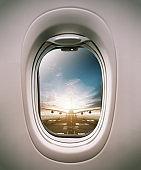 Airplane window view to runway with huge airplane