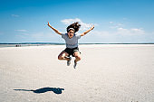 Portrait of woman jumping on the beach