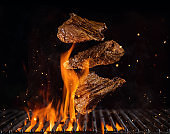 Flying beef steaks above burning grill grid