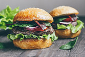 Homemade burger with beef, tomatoes, cheese, lettuce, spinach, arugula and onions on the rustic background