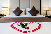 A red rose sits in the middle of a heart made from rose petals on a bed in a modern hotel room.