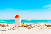 Sunblock bottle with starfish on the beach with blue sky. Summer time and travel concept.