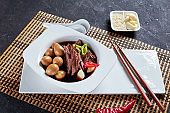 Jangjorim, beef braised in soy sauce served in white bowl with quail eggs, garlic cloves and chili pepper slices