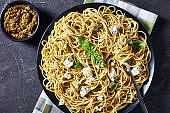 Spaghetti with genovese basil pesto and blue cheese on a black plate