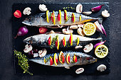 three whole raw mackerel with lemon, tomatoes, mushrooms, spices and herbs