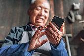 Chinese senior man using mobile phone