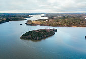 Aerial view of blue lake with island and green forests in Finland. Drone photography