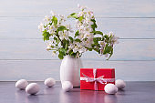 Easter eggs, red gift box and and apple tree branches