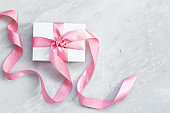 Gift or present box and sequins on marble table top view with copy space. Flat lay. Birthday, wedding or christmas concept
