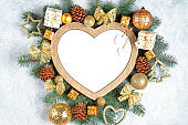 Christmas frame in the shape of a heart is surrounded by branches of a New Year tree Christmas decorations, Isolated on white background with copy space. Top view, flat lay