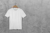 White Blank Cotton T shirt Hanging Center Gray Concrete Empty Wall Background with clipping path
