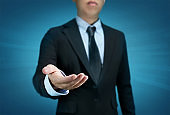 Businessman open hand on blue background