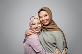 Portrait of attractive two young muslim girl having fun together isolated on grey background