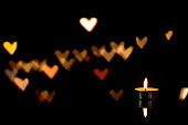 burning candle and heart shaped bokeh