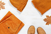Female orange knitted cap, scarf, pants, and leather boots on white wood background with autumn yellow leaves and with copy space. Autumn and Fashion concept with warm clothing. Top view.