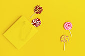 Lollypop sweet caramel candy on stick, yellow paper bag. Bright background for postcard, or invitation for Birthday, party, Hen-party. Copy space. Top view. Flat lay.