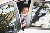 Adorable toddler girl in modern car seat