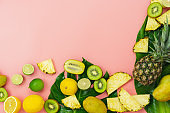 Table top view fruit tropical with spring summer holiday & vacation  background concept.Arrangement sliced various pineapple mango lemon and lime on monstera green leaves.Items on pink paper.pastel.