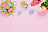 Table top view shot of decorations Happy Easter holiday background concept.Flat lay bunny eggs and tulip & rabbit doll on pink paper at studio office desk.Blank space design for mock up & template.