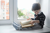 The little boy is reading a book. The child sits at the window and prepares for lessons. A boy with a book in his hands is sitting on the windowsill.