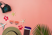 Table top view food items of travel summer holiday & vacation background concept.Flat lay arrangement of passport camera palm flower on modern rustic pink paper.copy space for creative design text