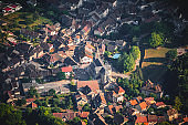 Aerial top view of Culoz small French village illuminated by first sunlight rays in the morning, with old church and residential houses, in Ain department Auvergne-Rhone-Alpes region