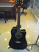 Black color guitar seen foots of man was in the musical instrument shop