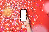Hand holding smart phone on red background
